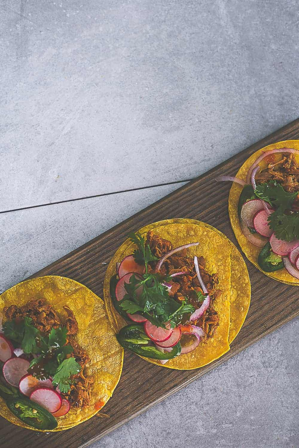 3 vegan jackfruit carnitas shown from the top on a brown board with toppings